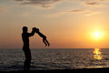 Father plays with son against a sunset on beach Stock Photo