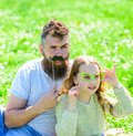 Father posing with mustache and child posing with eyeglasses photo booth attribute. Dad and daughter sits on grassplot Royalty Free Stock Photo