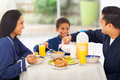 Father pouring milk loving in his son s corn flakes during breakfast Royalty Free Stock Images
