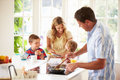 Father preparing family breakfast in kitchen with children and wife background Royalty Free Stock Photos