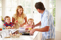 Father preparing family breakfast in kitchen looking at each other smiling Stock Image