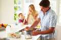 Father preparing family breakfast in kitchen the morning breaking eggs Stock Image