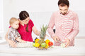 Father is preparing fruit for child in the kitchen Stock Photo