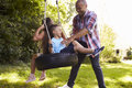 Father Pushing Children On Tire Swing In Garden Royalty Free Stock Photo