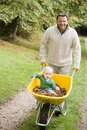 Father pushing young son in wheelbarrow Stock Photo
