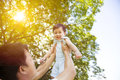 Father raising his little smiling son up high with natural background Stock Photography