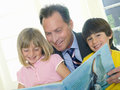 Father reading to son and daughter smiling portrait of boy tilt Royalty Free Stock Images