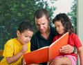 Father Reading with Young Son and Daughter Royalty Free Stock Photos