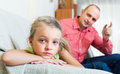 Father rebuking daughter for offence serious small in interior Stock Photos