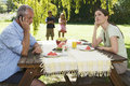 A father receiving a business call during a family lunch in the garden Royalty Free Stock Photo