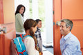 Father saying goodbye to children as they leave for school smiling at each other Stock Images