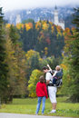 Father showing his kids the neuschwanstein castle young two a teenager boy and a toddler girl in germany in autumn Stock Image