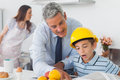 Father showing son his blueprints as he is wearing hardhat at home in kitchen before work Stock Images
