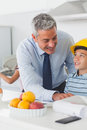 Father showing son his blueprints as he is wearing yellow helmet in the kitchen before work Stock Photo
