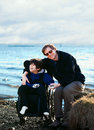 Father sitting with disabled son along lake shore in wheelchair by Stock Photography