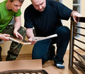 Father and son assemble cot Royalty Free Stock Photo