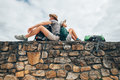 Father and son backpacker traveler rest together on old stone wa