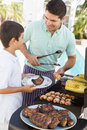 Father And Son Barbequing Royalty Free Stock Photos