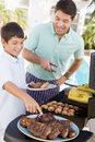 Father And Son Barbequing Stock Images