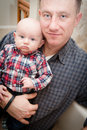 Father and son with blue eyes holding his infant baby Royalty Free Stock Image