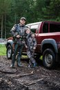 Father and son came to the forest for hunting together. Standing with a shotgun rifle in front of pickup truck. Royalty Free Stock Photo