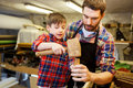 Father and son with chisel working at workshop