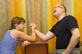 Father and son compete in arm wrestling sitting at home Royalty Free Stock Photos