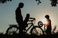 Father with son and daughter riding bikes at sunset Royalty Free Stock Photo