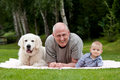 Father with son and dog lying on grass Royalty Free Stock Image