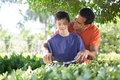 Father and son doing yard work together hispanic happily teaches his teenaged how to use hedge clippers to trim bushes in lush Royalty Free Stock Photo