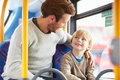 Father and son enjoying bus journey together sitting down on seat smiling at each other Royalty Free Stock Photo