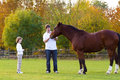 Father and son feeding a horse on a autumn day Royalty Free Stock Photo