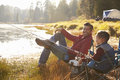 Father and son fishing by a lake, dad looks to camera Royalty Free Stock Photo