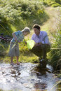 Father and son (6-8) fishing in shallow stream, boy looking in fishing net, side view Royalty Free Stock Photo