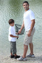 Father and son fishing together by a lake Royalty Free Stock Photos