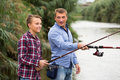 Father and son fishing together on lake Royalty Free Stock Photo
