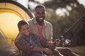 Father and son fishing together in park Royalty Free Stock Photo