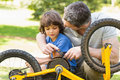 Father and son fixing bike closeup of Royalty Free Stock Photography
