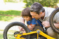 Father and son fixing bike side view of Stock Photos