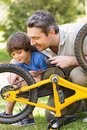 Father and son fixing bike side view of Royalty Free Stock Image