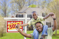 Father and son in front of real estate sign and home happy african american new sold Royalty Free Stock Photography