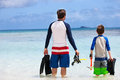 Father and son go snorkeling back view of with equipment fins mask at tropical beach Stock Images