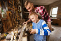 Father and son with hammer working at workshop happy family carpentry woodwork people concept little hammering nail into wood Stock Image