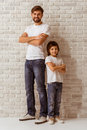 Father and son handsome young his cute little standing back to back looking in camera smiling both in white t shirts jeans Stock Photo