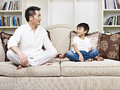 Father and son having a conversation on couch at home Royalty Free Stock Photos