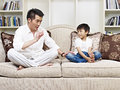 Father and son having a conversation on couch at home Stock Images