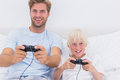 Father and son having fun playing video games in bed Royalty Free Stock Photos