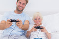 Father and son having fun playing video games in bed Stock Photo