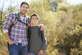 Father and son hiking in countryside wearing backpacks Stock Photos