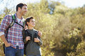 Father and son hiking in countryside wearing backpacks Stock Photography